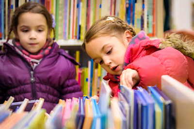 Two young girls looking through books