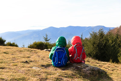 Two young children with backpacks sitting on a hill